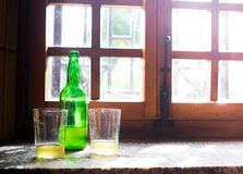 Green bottle of natural Cider with two traditional glasses window still life. Asturias, Northern Spain.