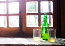 Green bottle of natural Cider with two traditional glasses window still life. Asturias, Northern Spain. Stock Photos