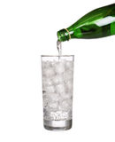 Green bottle pouring water in glass of cold mineral carbonated Stock Photography