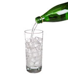 Green bottle pouring water in glass of cold mineral carbonated Royalty Free Stock Photo