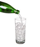 Green bottle pouring water in glass of cold mineral carbonated Royalty Free Stock Photos