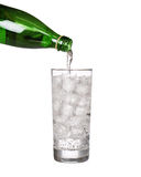 Green bottle pouring water in glass of cold mineral carbonated Stock Image