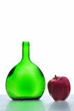 Green bottle and red apple. Green bottle with water drops and fresh red apple stock images