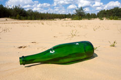 Green bottle in sands Stock Photos