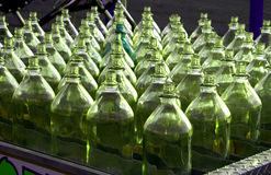 Green Bottles. Rows of green bottles lined up together with one dark green in the middle stock image