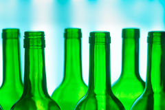Green Bottles. Bright green glass wine bottles against a colorful background Royalty Free Stock Photos