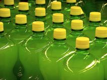 Green Bottles. With yellow caps aligned in a supermarket Stock Image