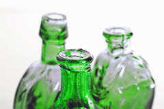 Green bottles in close up. Three green vintage bottles with soft focus on front bottle Royalty Free Stock Images
