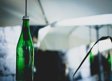 Green bottles on the ropes under umbrellas Stock Image