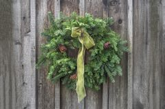 Green bow and Christmas wreath on wooden wall. Green satin bow on natural evergreen Christmas wreath hanging outdoors on an unpainted rustic wood plank wall royalty free stock image
