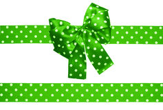 Green bow and ribbon with white polka dots made from silk Stock Photos