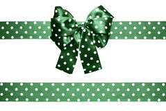 Green bow and ribbon with white polka dots made from silk Royalty Free Stock Images