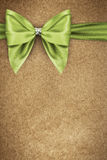Green bow on texture of paper packaging Royalty Free Stock Image