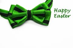 Green bow tie with black stripes. Beautiful colorful bright green bow tie with black stripes on white background with space for text as template for Happy Easter Royalty Free Stock Photos