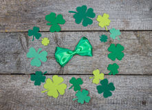 Green bow tie in circle of clover leaf on table Stock Photo
