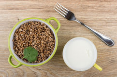 Green bowl with boiled buckwheat, cup of milk and fork Royalty Free Stock Photography