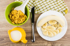 Green bowl with cornflakes, milk, knife and slices of bananas Royalty Free Stock Images