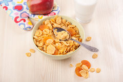 Green bowl of crunchy corn flakes for breakfast with apple on wo Royalty Free Stock Photography