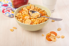 Green bowl of crunchy corn flakes for breakfast with apple Stock Images