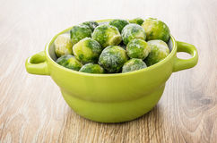Green bowl with frozen brussels sprouts on table Stock Photography