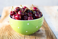Green bowl full of ripe cherry. Selective focus.  Stock Images