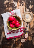 Green bowl with garden organic radish on dark wooden background Royalty Free Stock Image