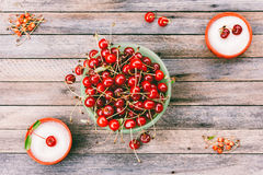 Green bowl with ripe cherry berries and cups with sugar on a wooden background Royalty Free Stock Photography