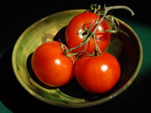 Green Bowl of Ripe Fresh Tomatoes. A treo of Ripe Fresh Tomatoes attached to a pruned Vine placed in a small green decorative pottery bowl with a dark background Royalty Free Stock Photos
