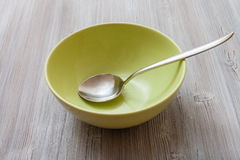 Green bowl with steel spoon on gray brown table. One green bowl with steel spoon on gray brown table Stock Images