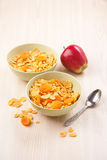 Green bowls of crunchy corn flakes for breakfast with apple on w Stock Images