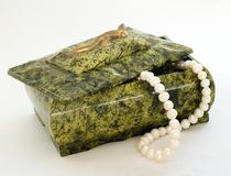 Green Box Wiht Pearl Necklace. Green casket made from serpentine ophite on a white background with lizard on top with pearl necklace stock image