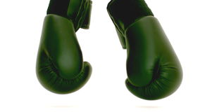 Green boxing gloves falling on the floor Stock Photography