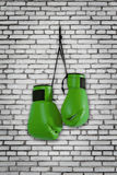 Green boxing gloves hanging on wall Royalty Free Stock Photography