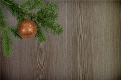 Green branch with christmas ball on wooden background Royalty Free Stock Image