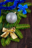 Green branch of fir, decorated with colorful ribbons and silver ball on dark wooden background. Royalty Free Stock Images
