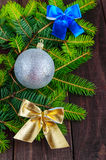 Green branch of fir, decorated with colorful ribbons and silver ball on dark wooden background. Royalty Free Stock Photography