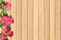 Green branch with pink spring flowers on wooden texture close-up. Green branch with pink spring flowers on wooden table texture close-up royalty free stock photos