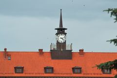 White clock with black arrows is on the roof of the house. royalty free stock photos