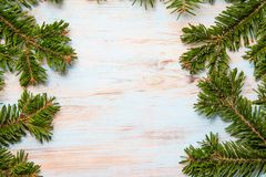Green branches of a Christmas tree on a blue board with a place for the inscription royalty free stock photo