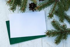 Green branches of a Christmas tree and cones on a white board background. Top view with copy space royalty free stock photo