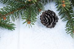 Green branches of a Christmas tree and cones on a white board background. Top view with copy space stock photos