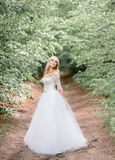 Green branches hang over the path where beautiful bride stands royalty free stock image