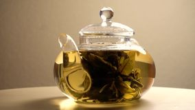 Green brewed tea in teapot. Spinning on wooden table stock video footage