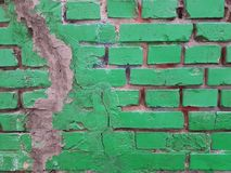 A green brick wall with a vertical crack closed with gray cement. Royalty Free Stock Photo