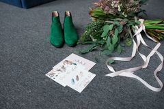 Green bridal shoes, rich green wedding bouquet with pink ribbons and a wedding complimentary lying on a grey floor. Wedding Royalty Free Stock Photos