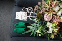 Green bridal shoes with wedding rings on them in focus, green wedding bouquet with pink ribbons and a wedding complimentary lying. On a grey armchair. Wedding Stock Photography