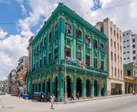 Green bright building in Havana Cuba surounded with people. Tourists and local people are walking and exploring beautiful old Havana in Cuba. Antique buildings Royalty Free Stock Image