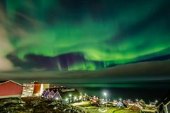 Green bright northern lights hidden by the clouds over the Inuit stock images