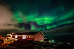 Green bright northern lights hidden by the clouds over living ho stock images