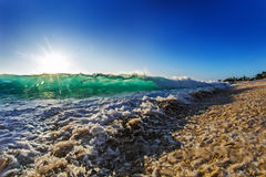 Green Bright Ocean Wave With The Sun. Beautiful Ocean Background Big Shorebreak Wave for Surfing. Hawaiian swell for sport activity. Power and Energy Of Nature Stock Photos